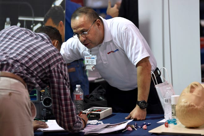 Luis Aguilar of MetroCare speaks with a job seeker during the Veteran's Job Fair Thursday at the Taylor County Expo Center's Round Building.