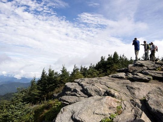 Hikers look over land that will soon be added to Mount Mitchell State Park, including Cattail Peak, in this 2016 photo.