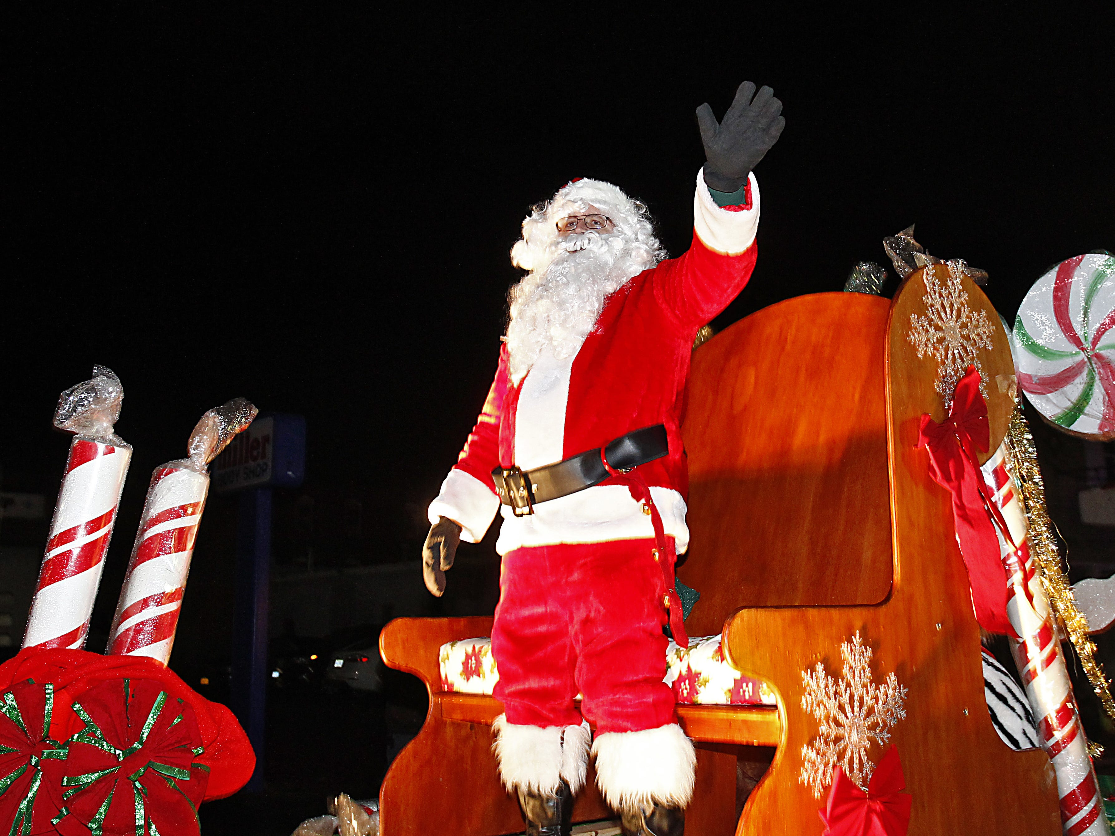 Santa waves to the crowd during the Johnson City Business and Professional Women's Holiday parade in downtown Johnson City on Dec. 3, 2015.