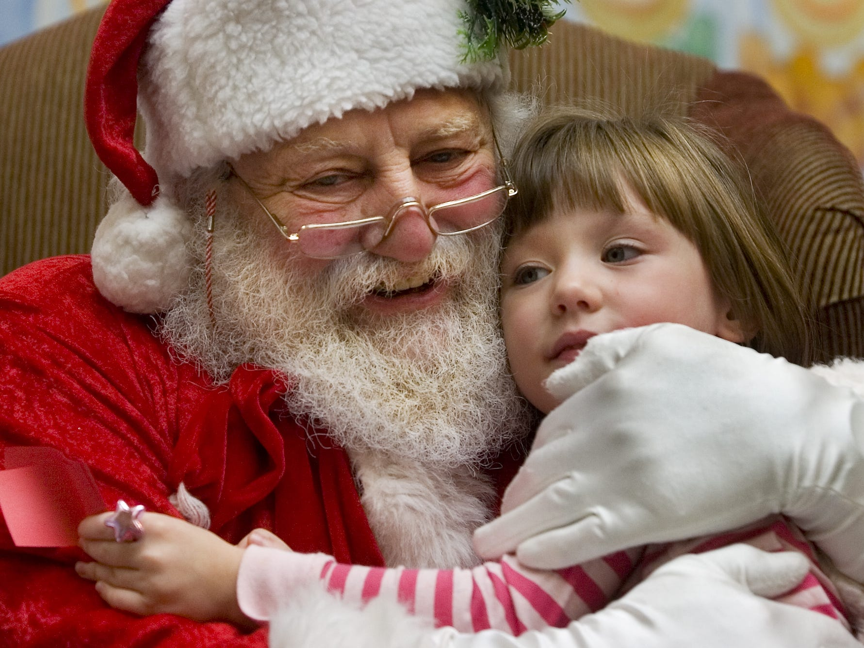"In 2007, Santa gives 4-year-old Hayley Laskowski, 4, of Vestal a hug while on duty with Gallery Photo at the Oakdale Mall. At the time, Hank Eynard had been playing Santa for 15 years. "" Who can ask for a better job, it makes me so happy to see their faces,"" he said."