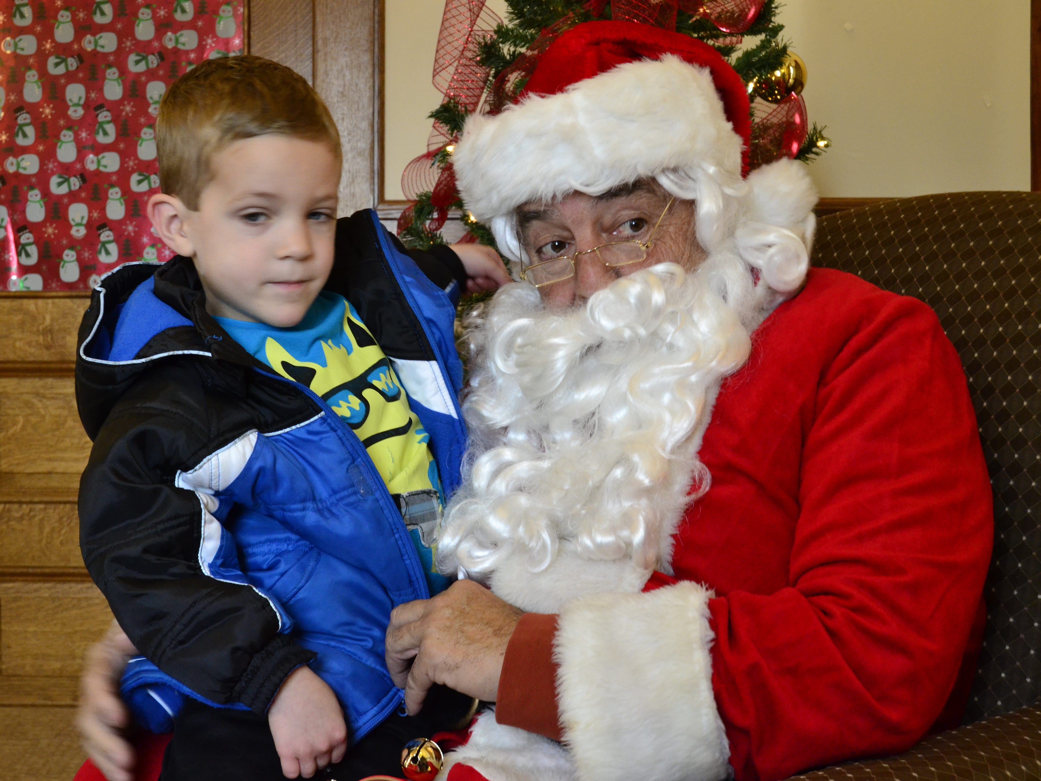 Joe Rombold, 4, from Endwell sits with Santa Sunday at the Vestal Coal House's third annual Christmas event for kids in 2015.