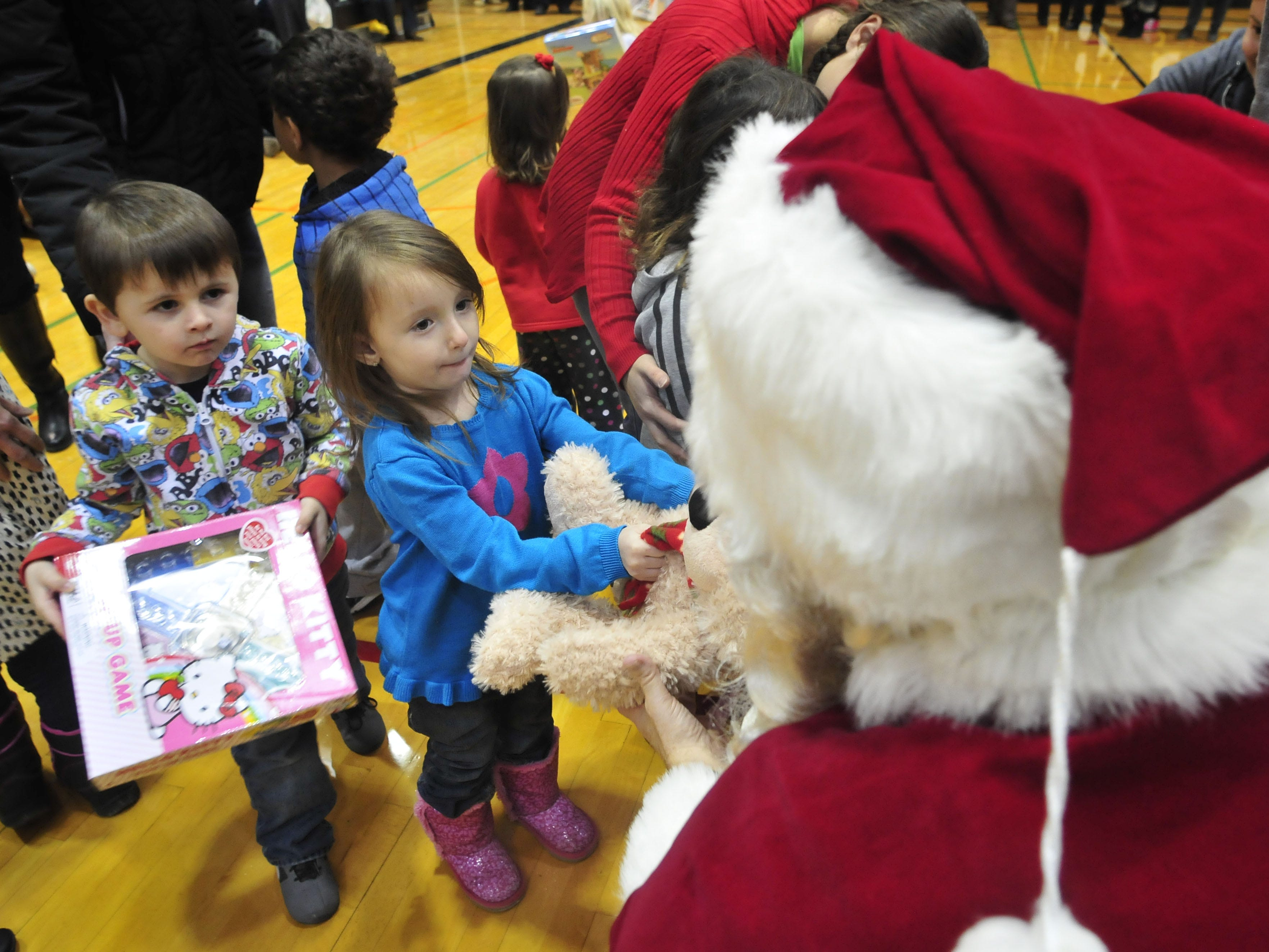 In 2013, Lily Davailus, 3, and Gavin Scheepsma, 4, both of Binghamton, hand Santa Claus toys during the 18th annual Giving of the Toys at SUNY Broome Community College. Brain Haas, below, a Binghamton resident and member of student assembly, helprf organize toys.