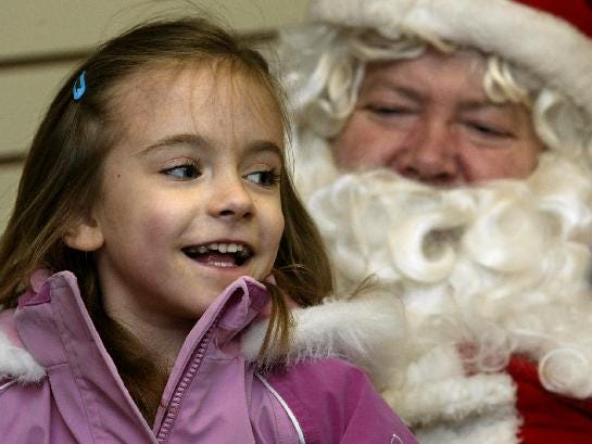 Alicia Twoey, 6, of Owego sits on Santa Ralph Warner's lap at the Tot Spot in downtown Owego during the Owego Holiday Showcase in 2003.