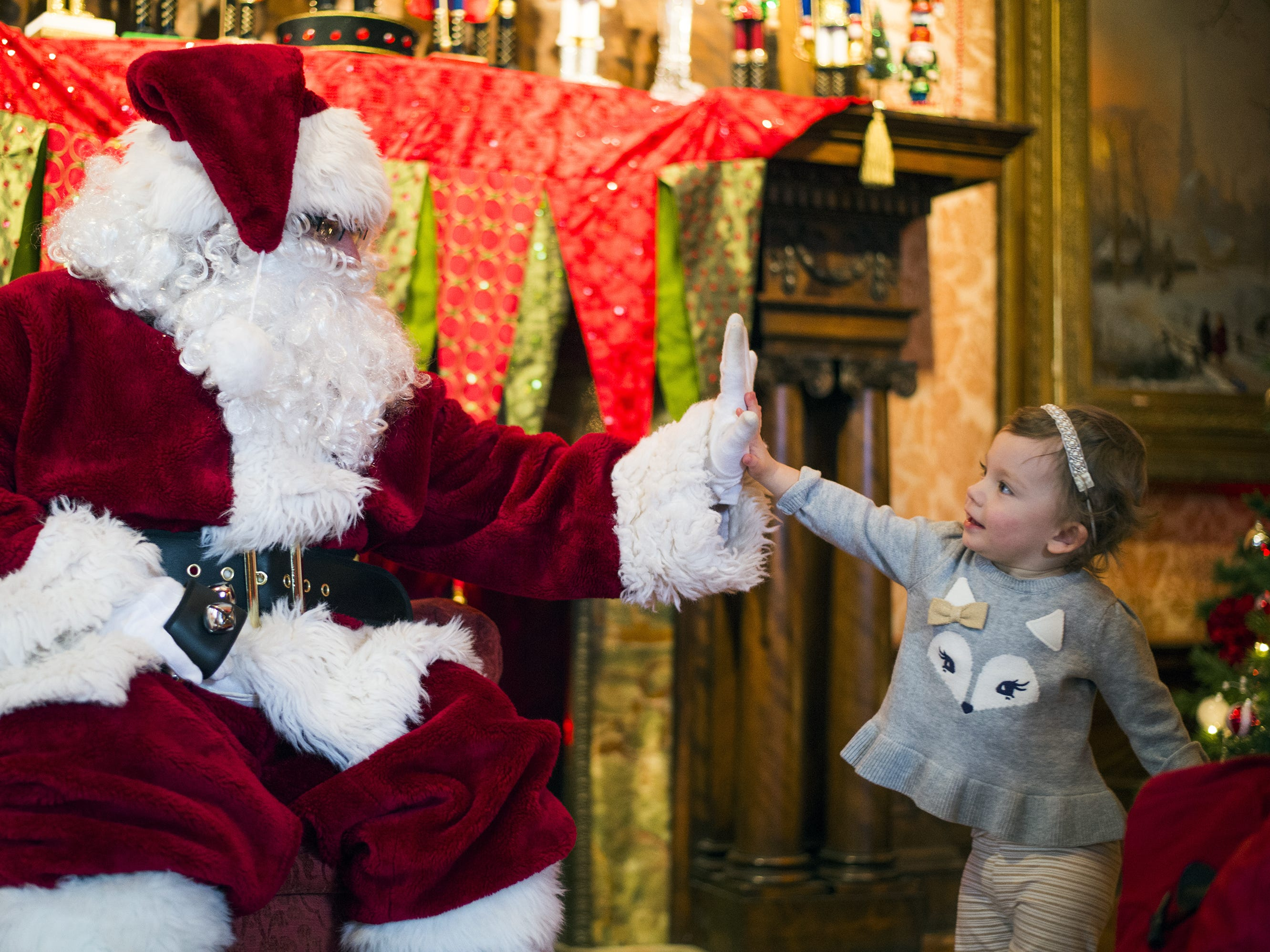 Emma Kinner, 1, of Binghamton, high-fives Santa at the Roberson Museum on in 2015.
