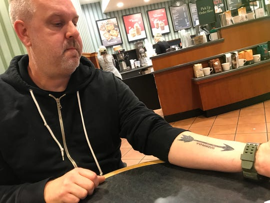 """Scott Jackowski shows off the tattoo he and his sister, Lori Hoban, got together. Jackowski said the arrow """"represents defense and protection from harm."""" The Roman numerals mark the date they found each other through DNA match."""