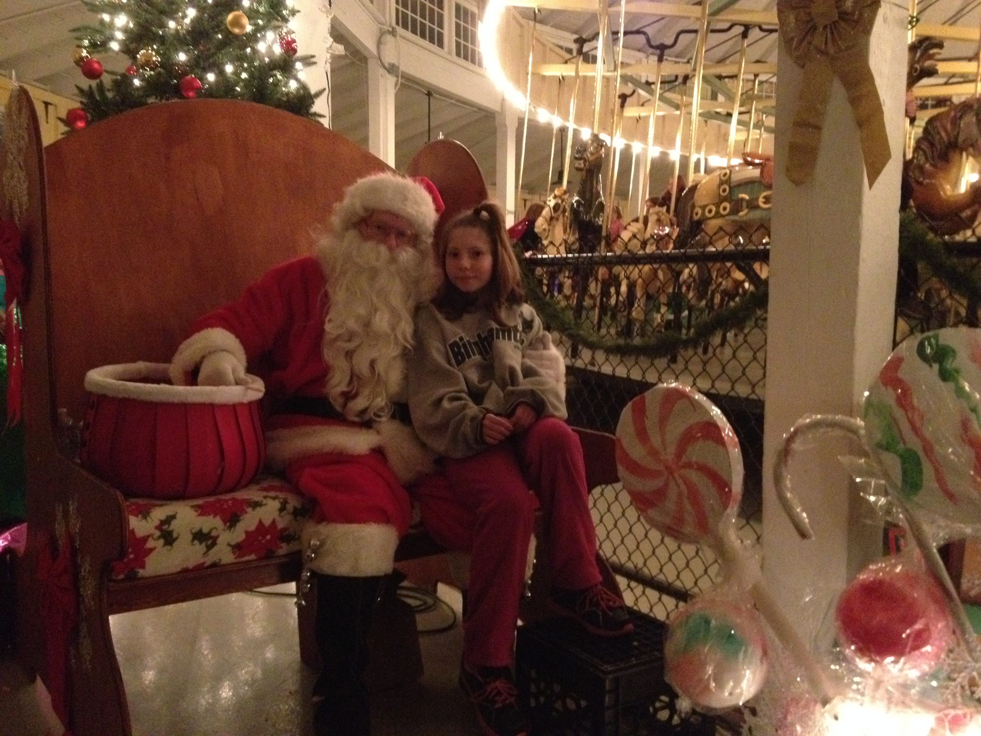 In 2013, Sarah Fresquez, 11, of Johnson City, sits on Santa Claus' lap while he reaches for a candy cane on Saturday night during the final weekend of the village's fourth annual Lights on the Carousel event.