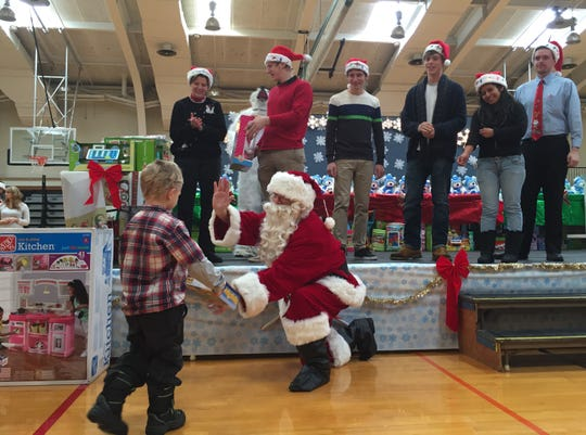 Grayson Burns, 4, of Binghamton, hands Santa Claus a gift on behalf of the BC Center at SUNY Broome Community College in 2014. Hundreds of toys collected by SUNY Broome student groups were donated to help the Toys for Tots program.