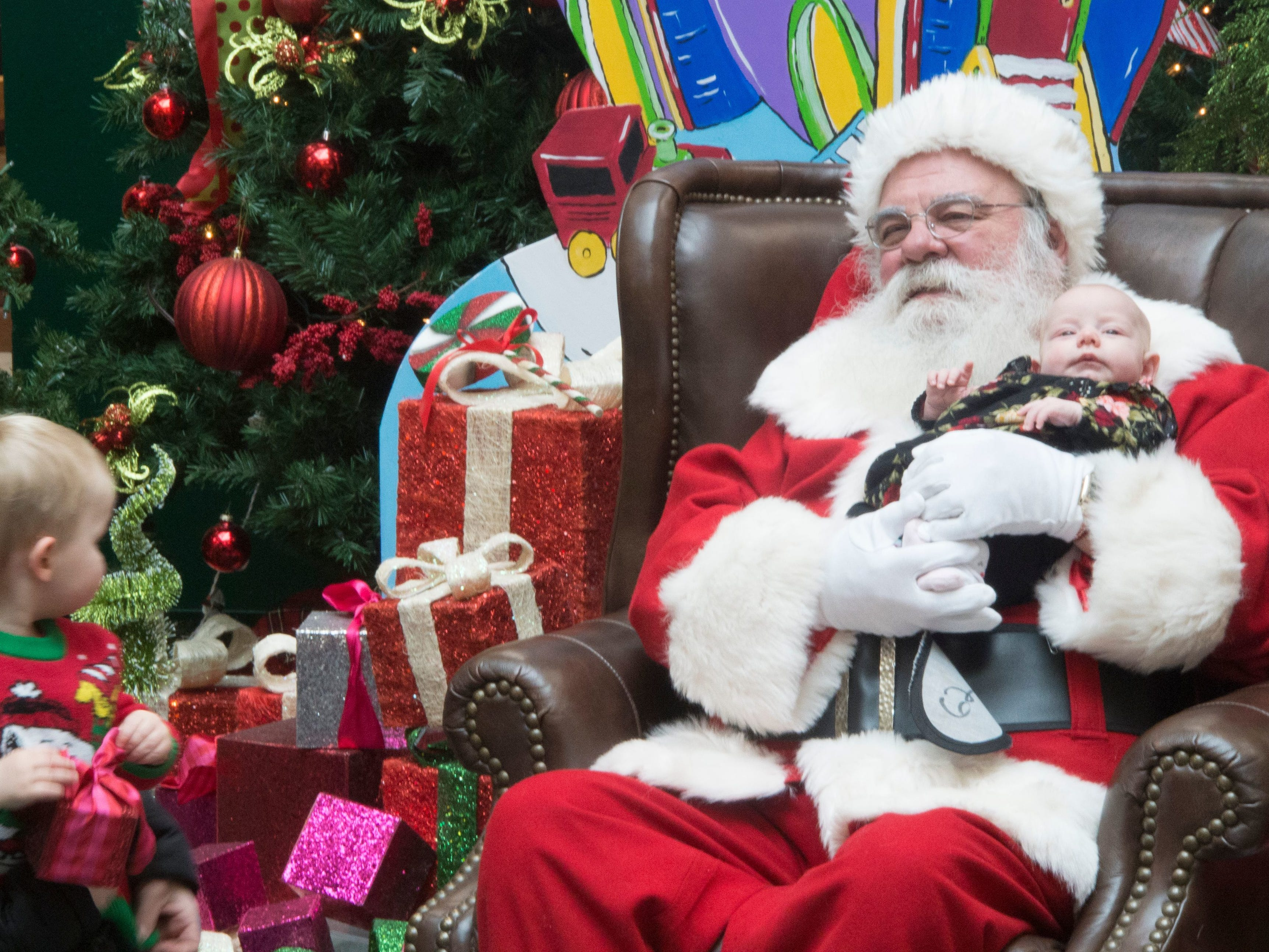In 2017, Santa holds Annika Tompkins while mom Sheila Darrow tries to persuade her son, Logan Tompkins, 2, to join the picture. Logan stood just close enough to Santa for a photo, but wasn't willing to go too far from his mom.