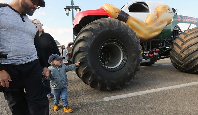 Jason and Lisa Minters are in awe of the Monster Trucks along with their son Jedi, 3, during Jedi's Special Day, hosted by the City of Port Orchard at the Port of Bremerton boat launch across from Port Orchard's City Hall on Wednesday, November 7, 2018. Jedi has been fighting leukemia for the last year and a half.