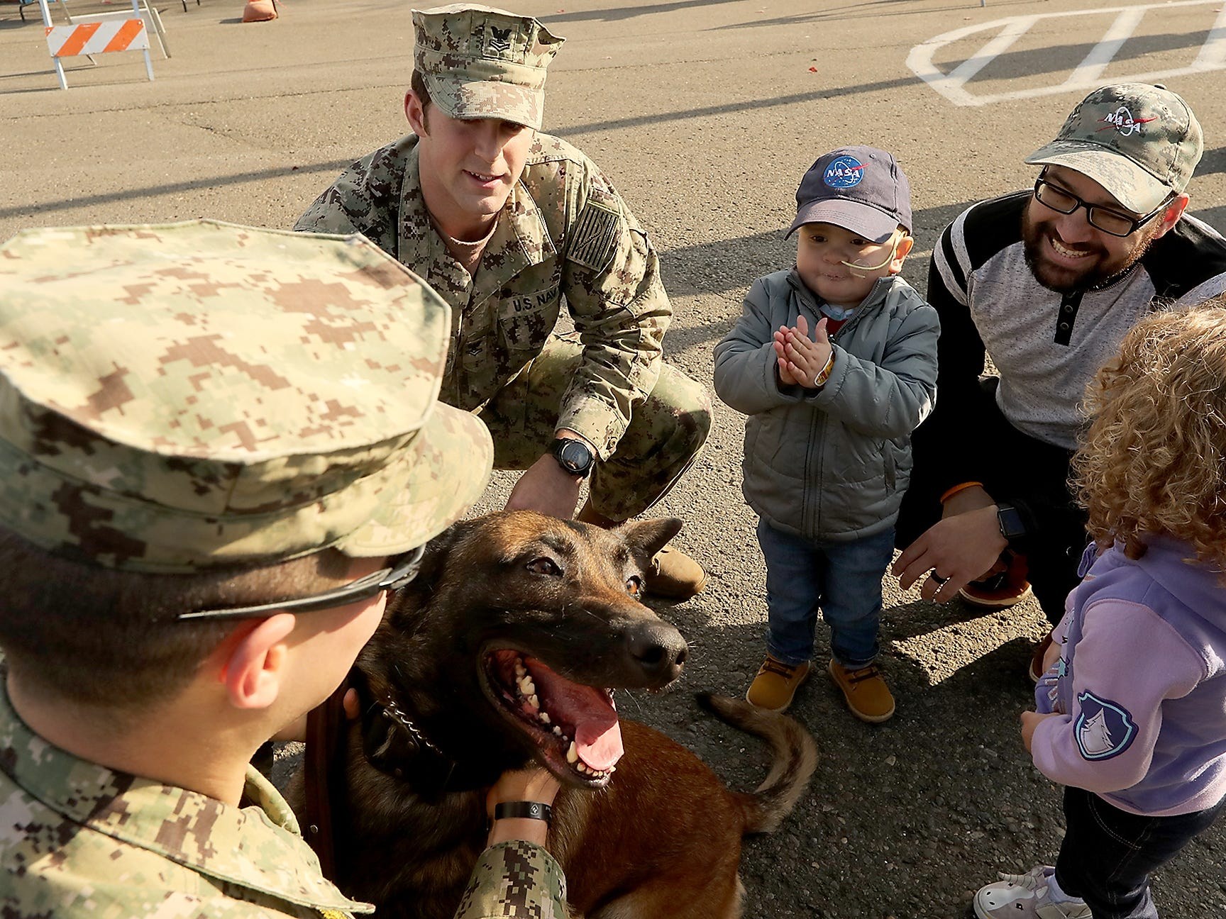 Naval Base Bangor's Robert Dorato (left) and William Patterson (center) introduce Dorato's Military Working Dog (MWD) Bbrazas to three-year-old Jedi Minters, his father Jason during Jedi's Special Day on Wednesday, November 7, 2018.
