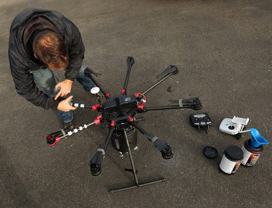 Andrew Biddle of Roof Tec prepares Roy, his drone, to spread moss treatment on the roof of customer Bonnie Boyle's Seabeck home on Thursday.