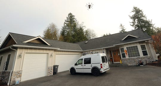 Roof Tec's drone spreads moss treatment on the roof of Bonnie Boyle's Seabeck home Thursday.