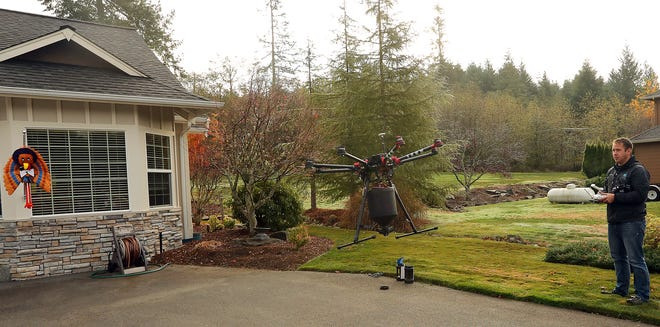 Roof Tec's Andrew BIddle pilots his drone above customer Bonnie Boyle's Seabeck home on Thursday.