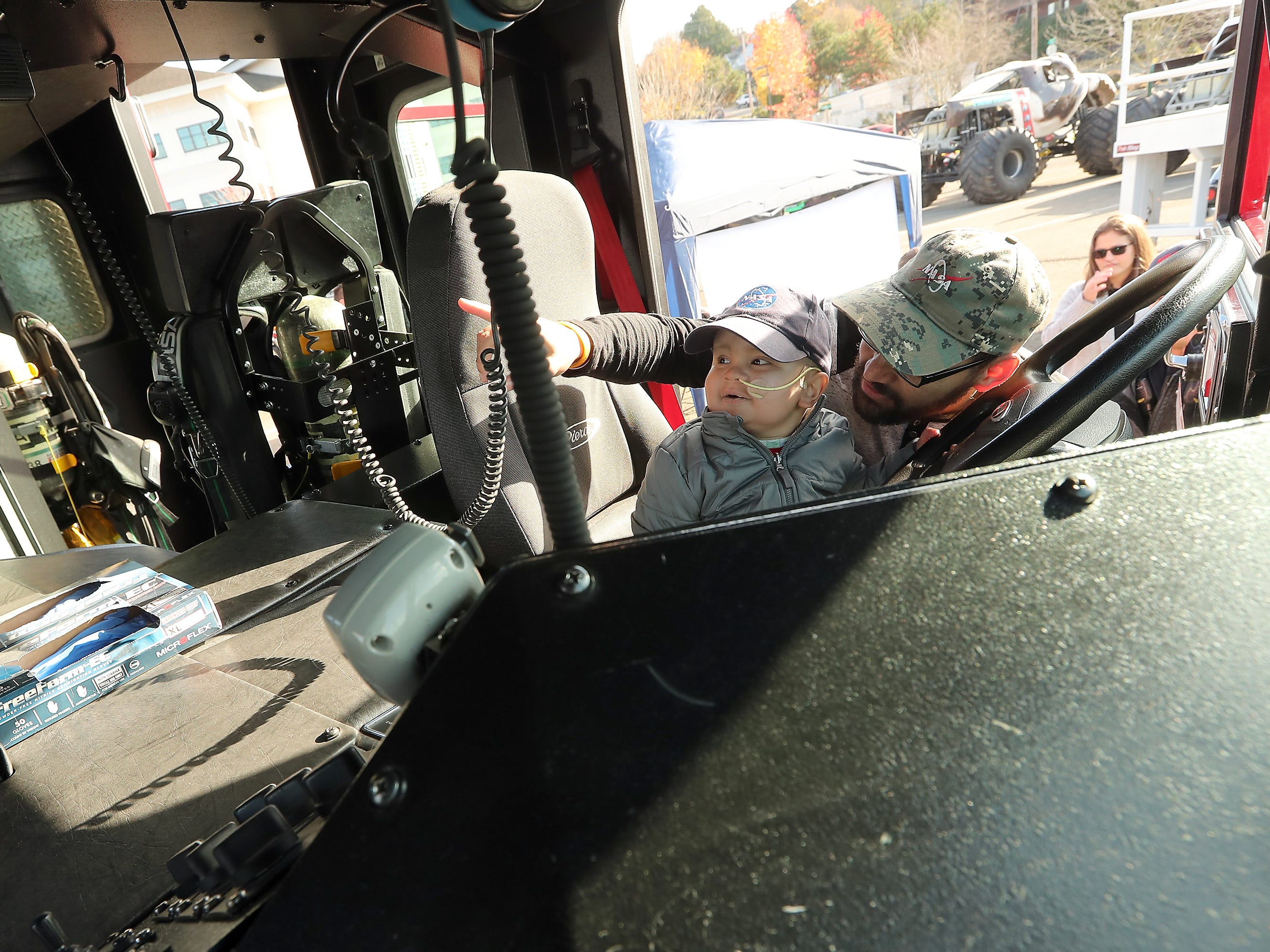 Three-year-old Jedi Minters and his father Jason take a look at the inside of South Kitsap Fire and Rescue's Ladder 31 on Wednesday, November 7, 2018.