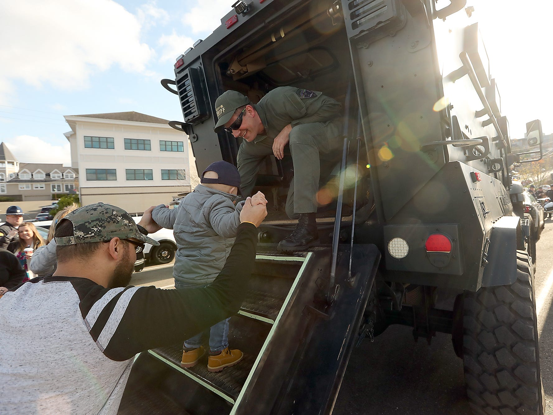 Kitsap County Sheriff's Sgt. Kurtis Lont (right) helps guide Jedi Minter, 3, and his father Jason up the stairs to tour the inside of an armored rescue vehicle at the Port of Bremerton boat launch in Port Orchard on Wednesday, November 7, 2018.