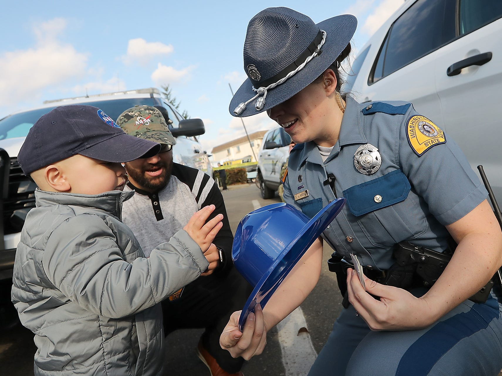 Trooper Chelsea Hodgson presents Jedi Minters, 3, with a Washington State Trooper hat and badge stickers during the Jedi's Special Day event at the Port of Bremerton boat launch across from Port Orchard's City Hall on Wednesday, November 7, 2018.