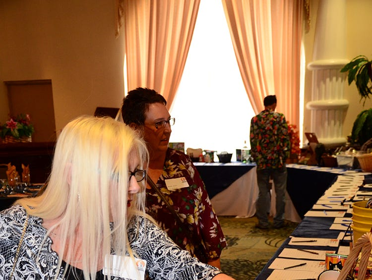 Wanda Gates and Kristine Goulet scan over items to bid on Saturday evening at the Space Coast Feline Network Autumn Gala held at the Space Coast Convention Center in Cocoa.