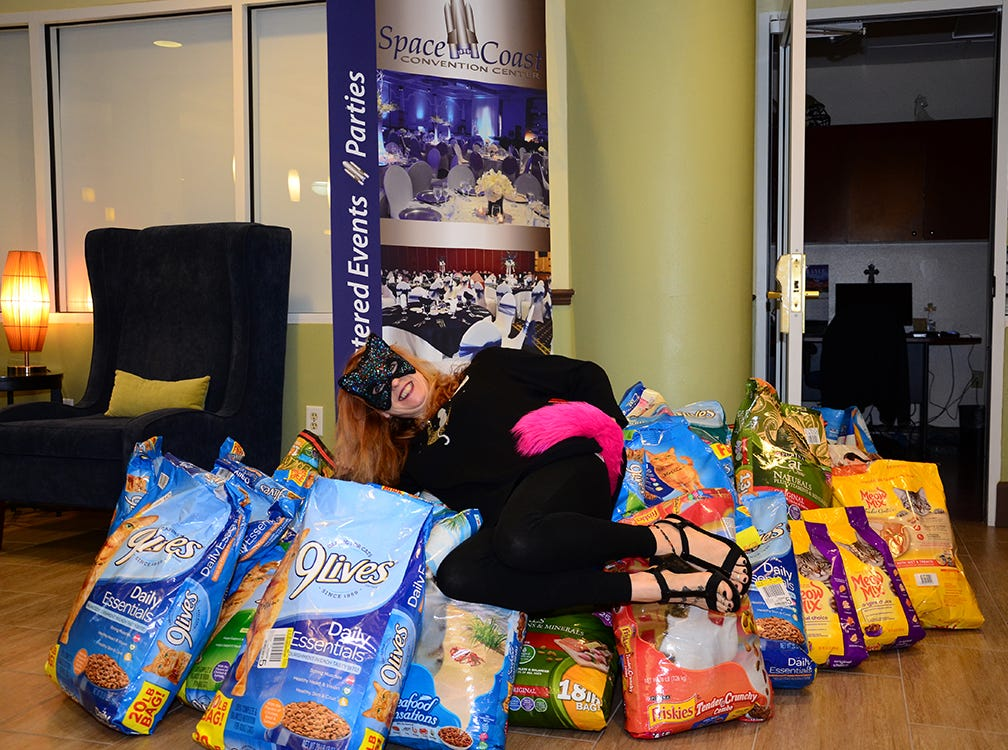 Naomi Bergner lays upon the many donated bags of cat food during the Space Coast Feline Network Autumn Gala held Saturday night.