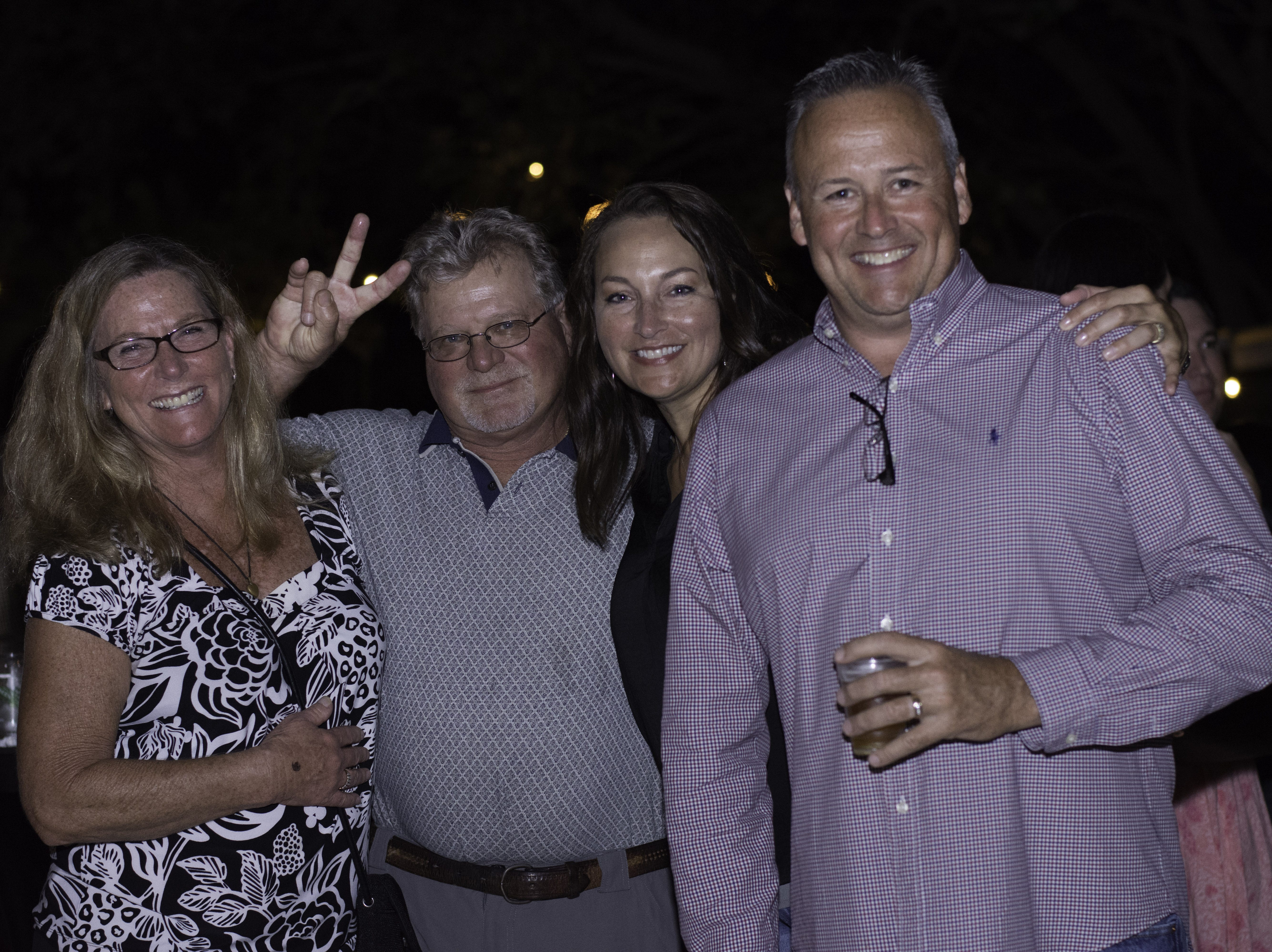 Jenny and Dennis Atkins stand with Missy and Garrett Lamp for a photo at the Acoustic Wine Lounge at Jazzoo.