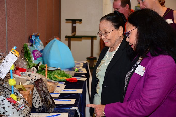 Margaret Meyers and Hisako Clark also enjoyed looking at items up for silent auction Saturday night at the Space Coast Feline Network Autumn Gala.