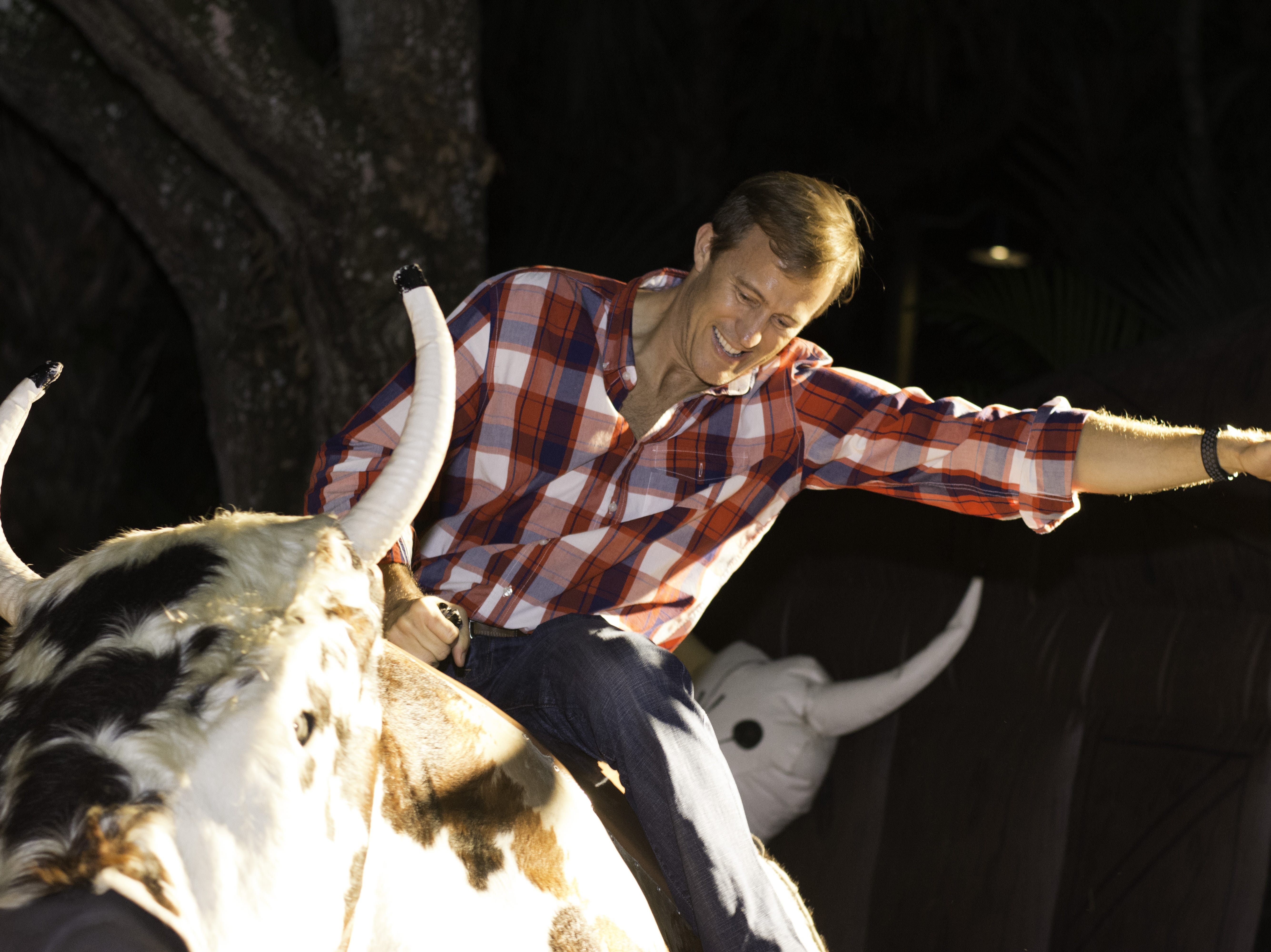 A guest attempts to not get bucked off the mechanical bull at Jazzoo in the country music venue.