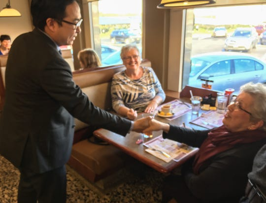 Andy Kim - self-declared 3rd Congressional District victor - shakes hands with Vicki Treutel of Willingboro at the Golden Dawn Diner Thursday. Treutel - seated across the table from jackie Young, of Cinnaminson - usually sit in the same booth every day. Kim took their seats as he met with press.