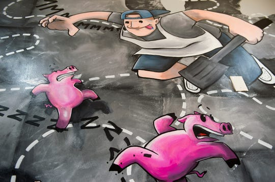A mural showing the family chasing pigs adorns the wall of Macona BBQ in Collingswood.