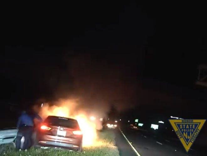 New Jersey State Police troopers rescue a man from a burning car on Route 42 in this still image taken from a police dashboard camera video.
