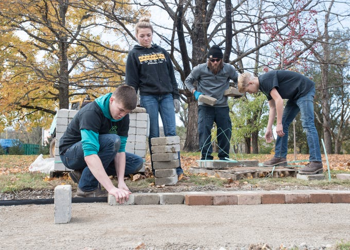 Skills USA students from Pickaway-Ross Career and Technology Center laid stone pavers at the Veteran's Healing Garden outside the Mace House Wednesday afternoon in Chillicothe.