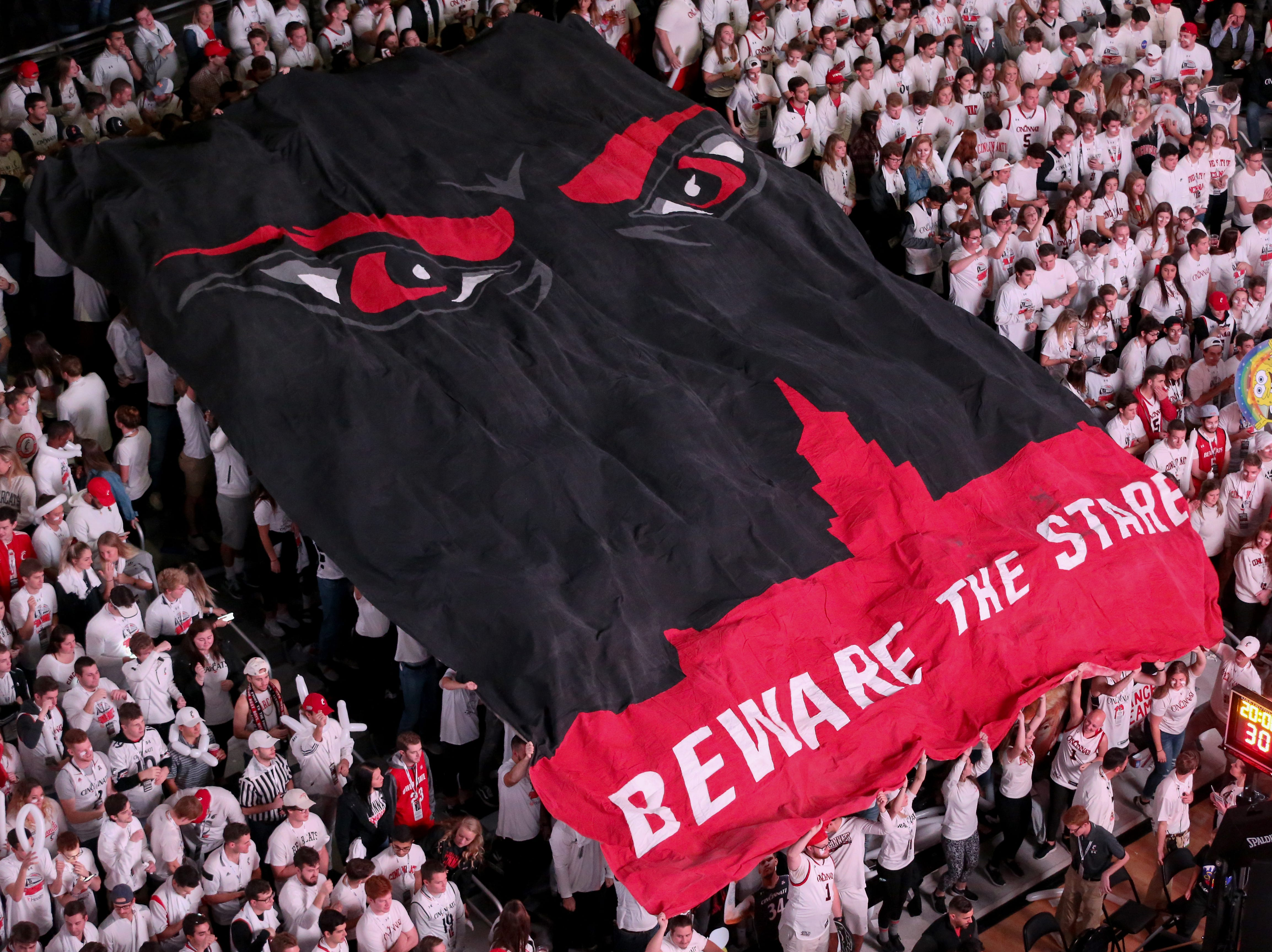 The Cincinnati Bearcats student section unfurls a flag before a college basketball game between the Ohio State Buckeyes and the Cincinnati Bearcats, Wednesday, Nov. 7, 2018, at Fifth Third Arena in Cincinnati.