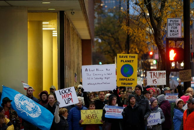 Demonstrators complete a loop of downtown during a nationwide protest following the resignation of attorney general Jeff Sessions and President Donald Trump's appointment of Matthew Whitaker at Piatt Park in downtown Cincinnati on Thursday, Nov. 8, 2018.