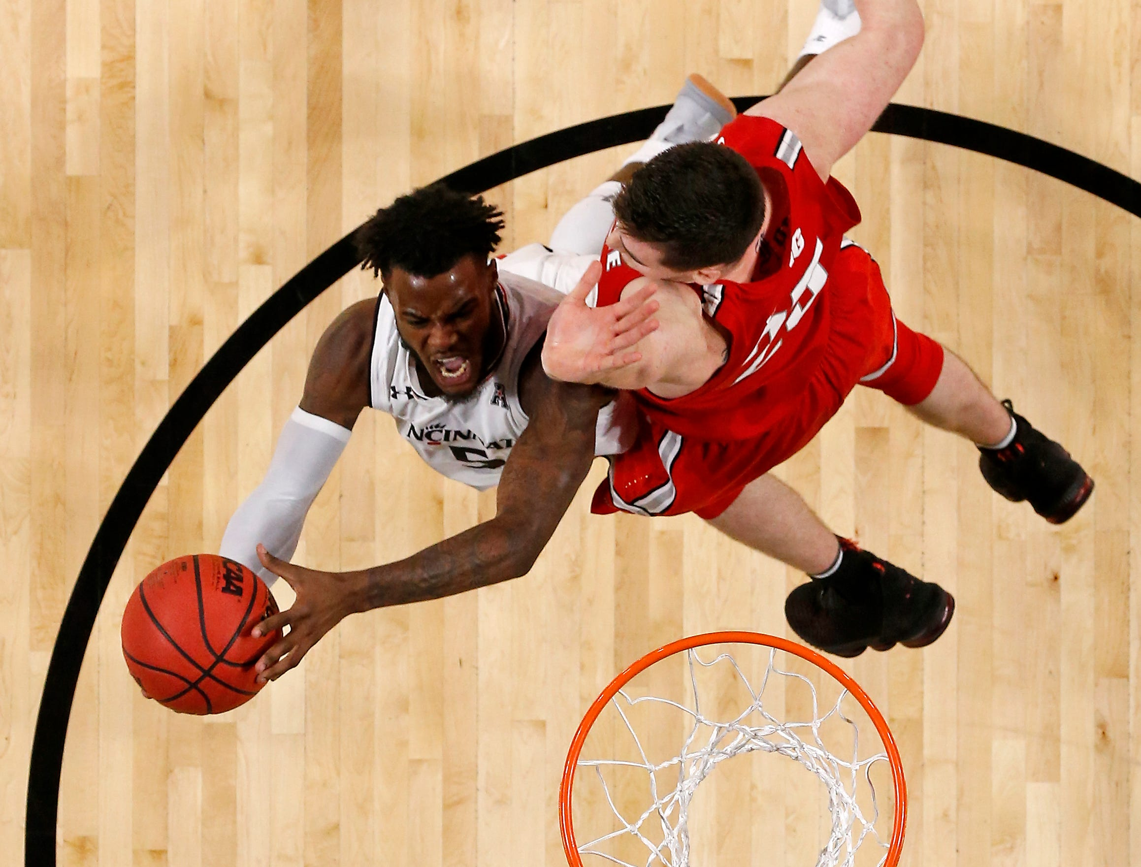 Cincinnati Bearcats guard Trevor Moore (5) shoots a layup past Ohio State Buckeyes forward Kyle Young (25) in the second half of the NCAA basketball game between the Cincinnati Bearcats and the Ohio State Buckeyes at Fifth Third Arena in Cincinnati on Wednesday, Nov. 7, 2018. The Bearcats opened the season 0-1 with a 64-56 loss the Ohio State.
