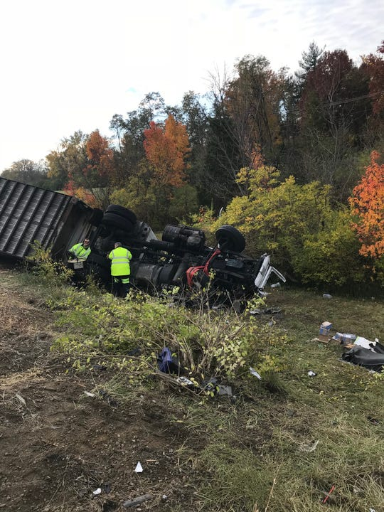 Crews work to upright a FedEx tractor-trailer following a Thursday morning crash on Interstate-275 in Northern Kentucky.