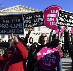 A crowd gathers outside the U.S. Supreme Court in...