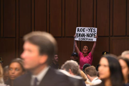 A woman disrupts Supreme Court nominee Brett Kavanaugh's confirmation hearing in October.