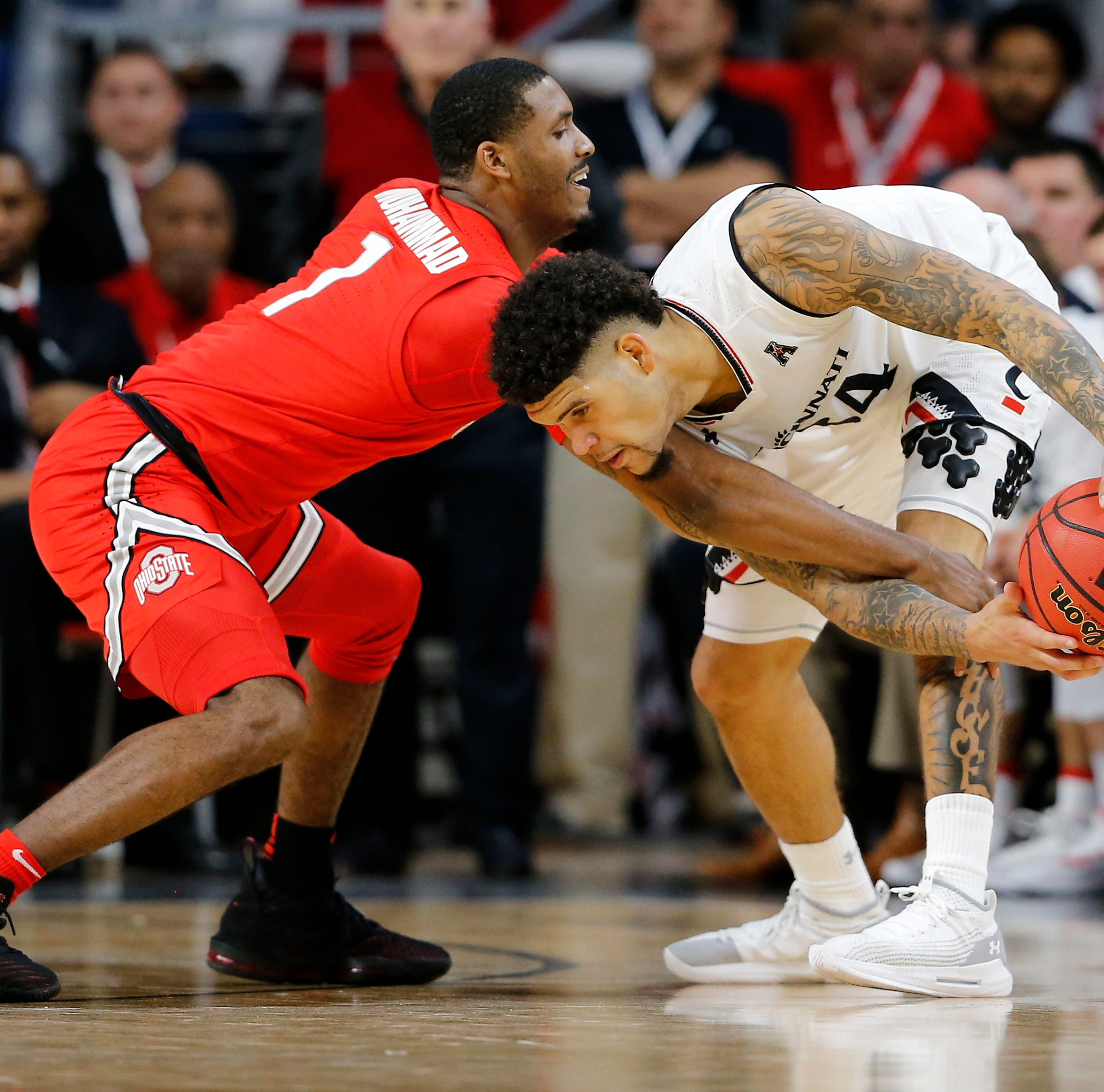Cincinnati Bearcats guard Jarron Cumberland (34) protects the ball from Ohio State Buckeyes guard Luther Muhammad (1) in the second half of the NCAA basketball game between the Cincinnati Bearcats and the Ohio State Buckeyes at Fifth Third Arena in Cincinnati on Wednesday, Nov. 7, 2018. The Bearcats opened the season 0-1 with a 64-56 loss the Ohio State.