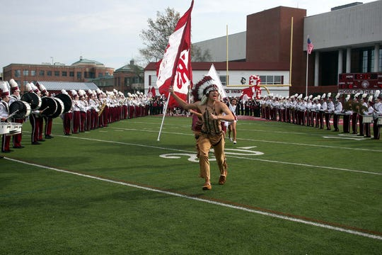 The Toms River South indian chief mascot leads the spirit flag crew through the marching band line at the start of a game in 2012.