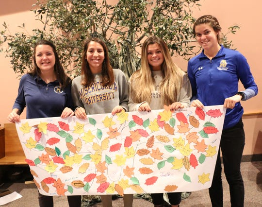 Misericordia University occupational therapy students Megan Peace, Old Saybrook, Conn.; Julianna Norris, Edison, N.J.; Clare Schoen, Scranton, Pa., and Taylor Webb, Clark, N.J., show off the handiwork from some of the students who participated in a collaborative mentoring project at Rock Solid Academy.