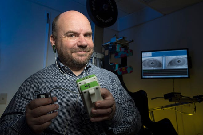Associate Professor of Pharmacology Physiology and Neuroscience Jorge Serrador holds stochastic noise sub-sensory stimulator, which improved balance in 100 percent of the veterans with Gulf War Illness who wore it.