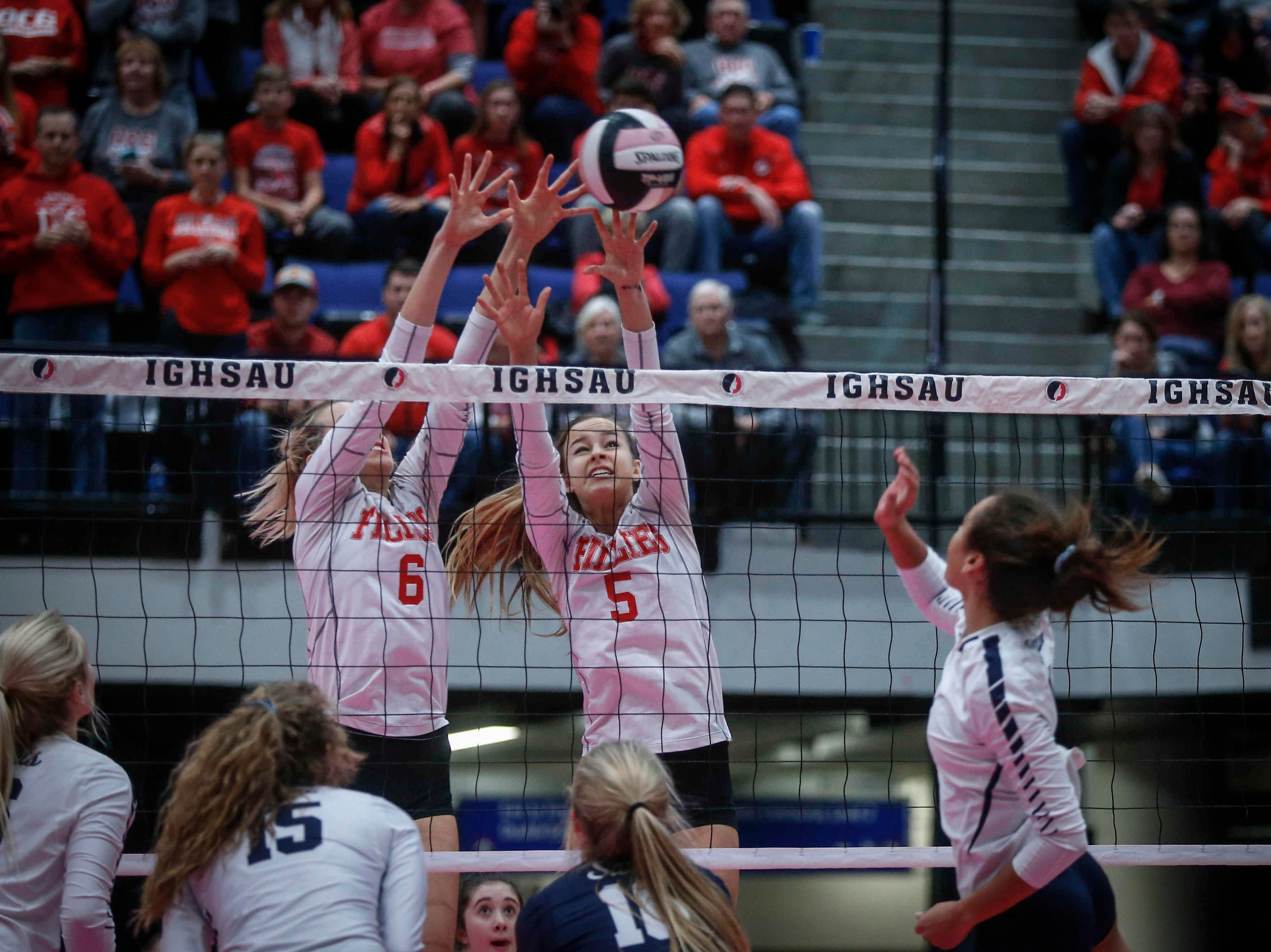 Dallas Center-Grimes seniors Tiffany Denger, left, and Hannah Ashley reach for the ball against Cedar Rapids Xavier in Class 4A during the 2018 Iowa High School state volleyball tournament on Thursday, Nov. 8, 2018, in Cedar Rapids.