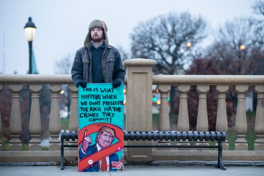 Alexandre Shiffer, of Des Moines, holds a sign during a rally at the Iowa State Capitol Grounds urging President Donald Trump to not to end the Mueller investigation, on Thursday, Nov. 8, 2018, in Des Moines.