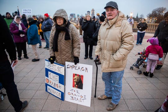 Barbara and Kirk Paulding, of Knoxville, join the crowd of about 100 people for a rally at the Iowa State Capitol Grounds urging President Donald Trump to not to end the Mueller investigation, on Thursday, Nov. 8, 2018, in Des Moines.