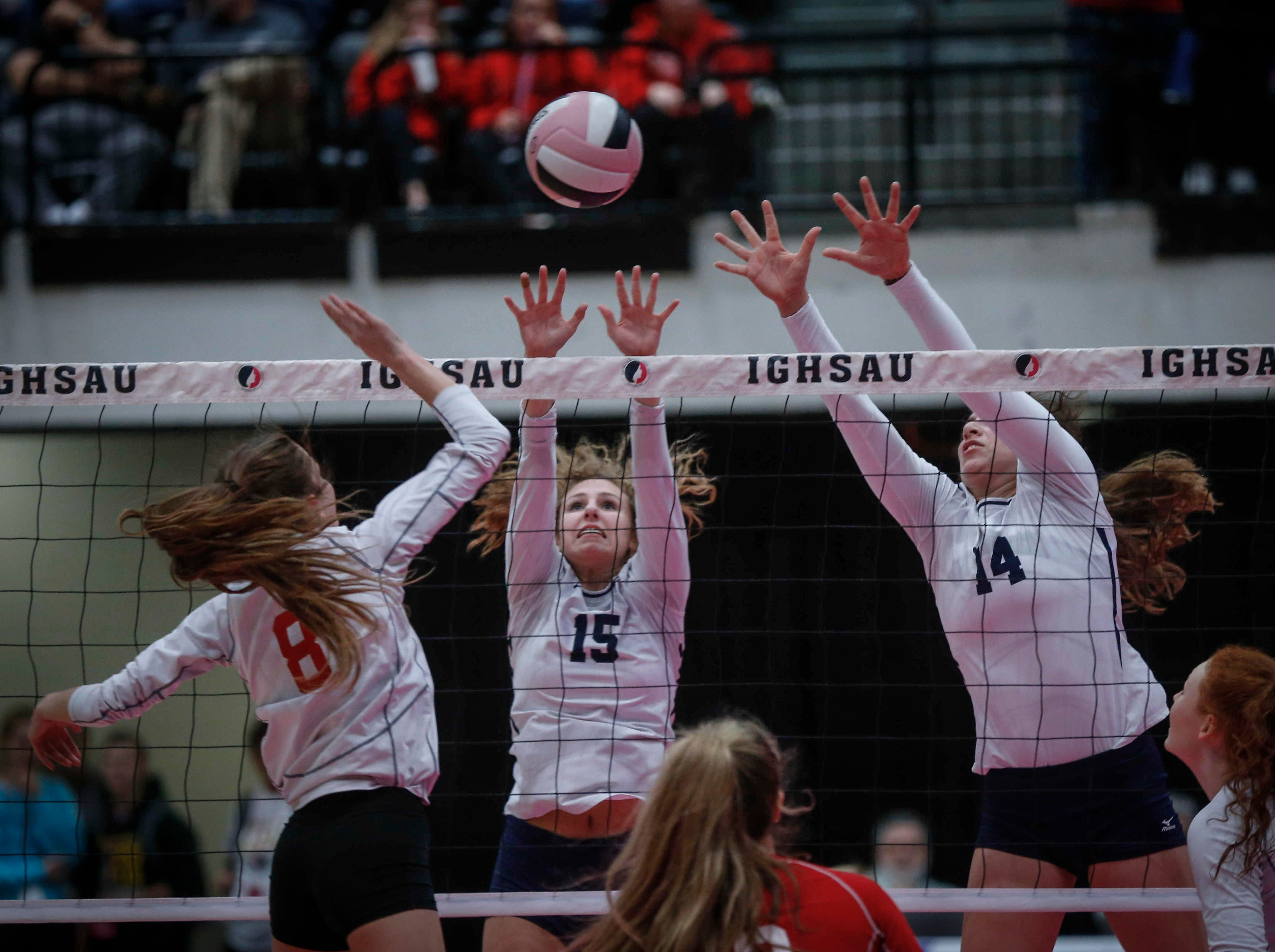 Dallas Center-Grimes junior Katelyn Knudsen, left, pushes the ball over Cedar Rapids Xavier's Jazmine Yamilkoski (No. 15) and Olivia Richardson in their Class 4A match during the 2018 Iowa High School state volleyball tournament on Thursday, Nov. 8, 2018, in Cedar Rapids.