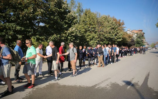 A long line of school children and locals in Krusha e Madhe greet Iowa Guardsmen and Kosovo Security Force members during a tour of their city and memorials Sept. 19, 2018, in Kosovo.