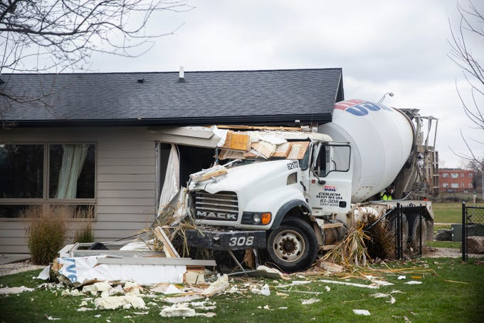 The Des Moines Police Department investigates a crash involving a cement truck colliding with a home at the corner of Martin Luther King Jr. Parkway and Cottage Grove Avenue on Thursday, Nov. 8, 2018, in Des Moines. Another car was also involved in the crash and the driver was sent to the hospital.