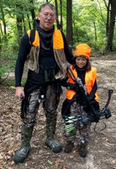 Kevin Donley readies to bow-hunt in Jackson with his daughter, Samantha, 8, on Sept. 22, 2018, during the annual Michigan Youth Hunt.