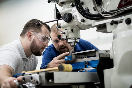 Chris Hunt, Technical Trainer, teaches one of Brose's Mechatronics Apprentices, Jake Stubbs, how to remove material using a mill. Brose leverages its robust apprenticeship programs to fill technician positions with highly trained apprentices.