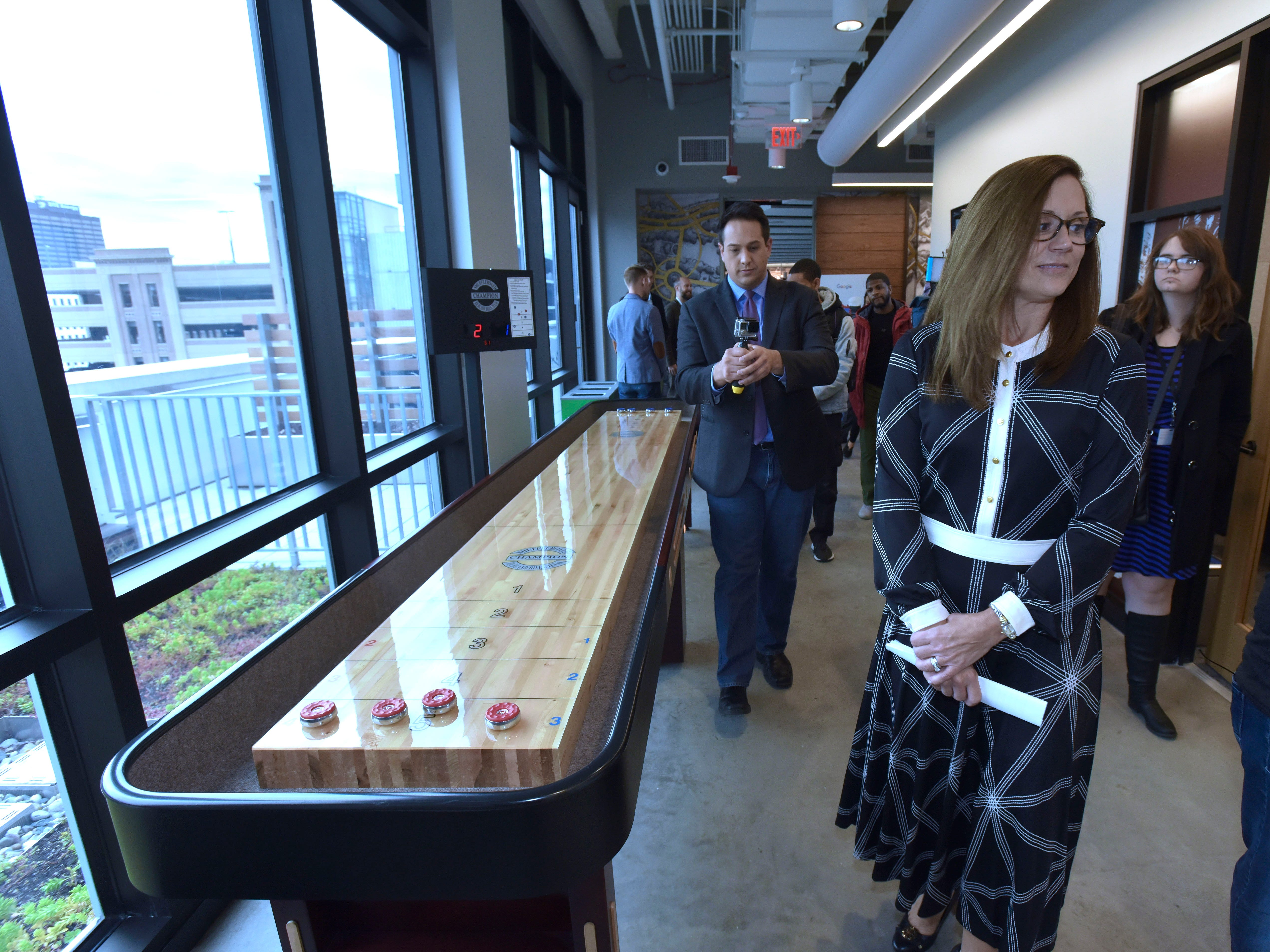 Danielle Russell, Google Detroit Site Leader, walks past a shuffle board table in the hallway during the media tour.