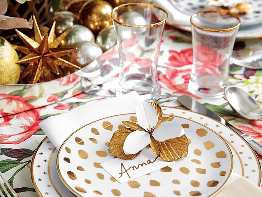 : A fashionable cheetah print goes glam in gold, in accent plates topping Bunny Williams' Gold Star bordered plates from Ballard Designs, which pop on a bold floral-patterned cloth. The centerpiece is a silver metal container stacked with gold and silver ornaments.