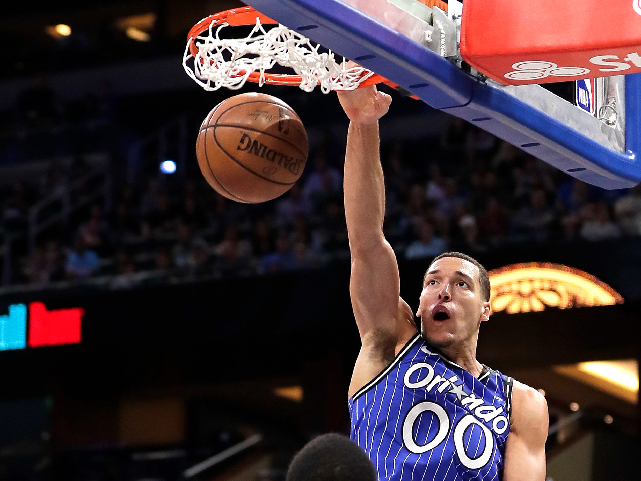 Orlando Magic's Aaron Gordon (00) dunks the ball in front of Detroit Pistons' Andre Drummond (0) during the first half of an NBA basketball game.